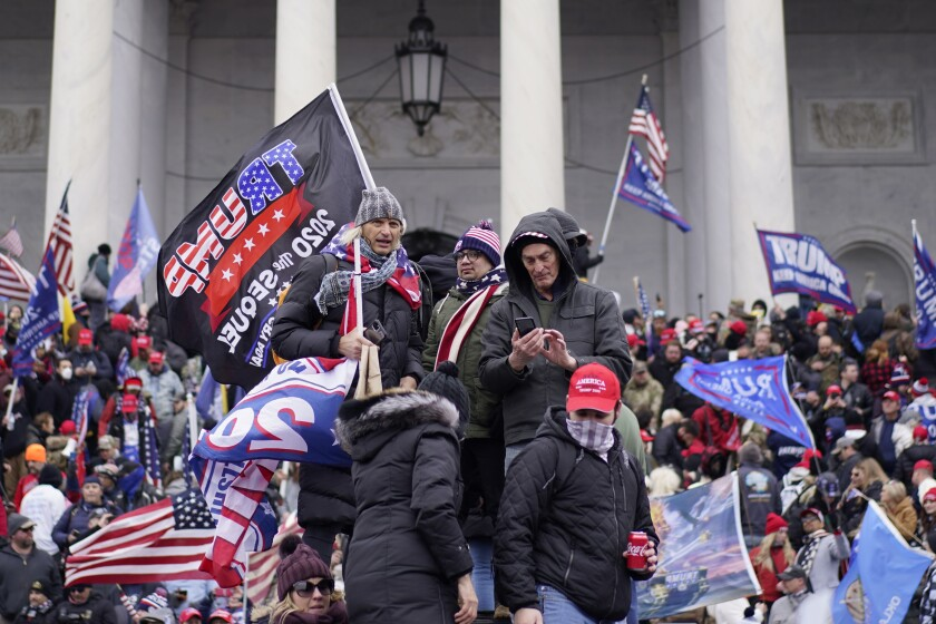 A mass of people with Trump 2020 flags and U.S. flags on the steps of the Capitol