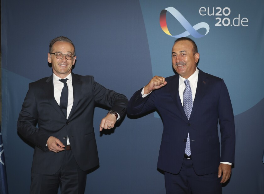 Turkey's Foreign Minister Mevlut Cavusoglu, right, and Germany's Foreign Minister Heiko Maas greet each other by using their elbows before a meeting, in Berlin, Thursday, July 2, 2020. (Cam Ozdel/Turkish Foreign Ministry via AP, Pool)