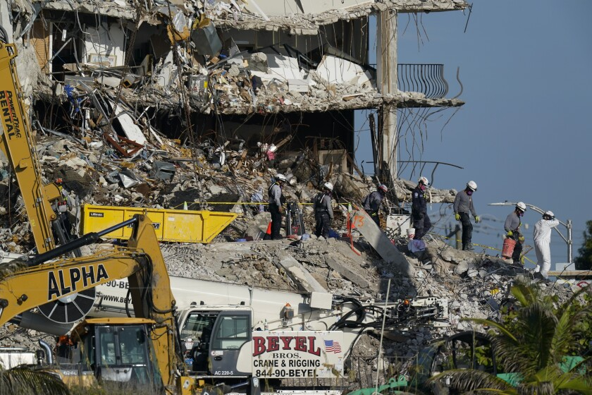 Rubble and rescue workers at site of condo tower collapse