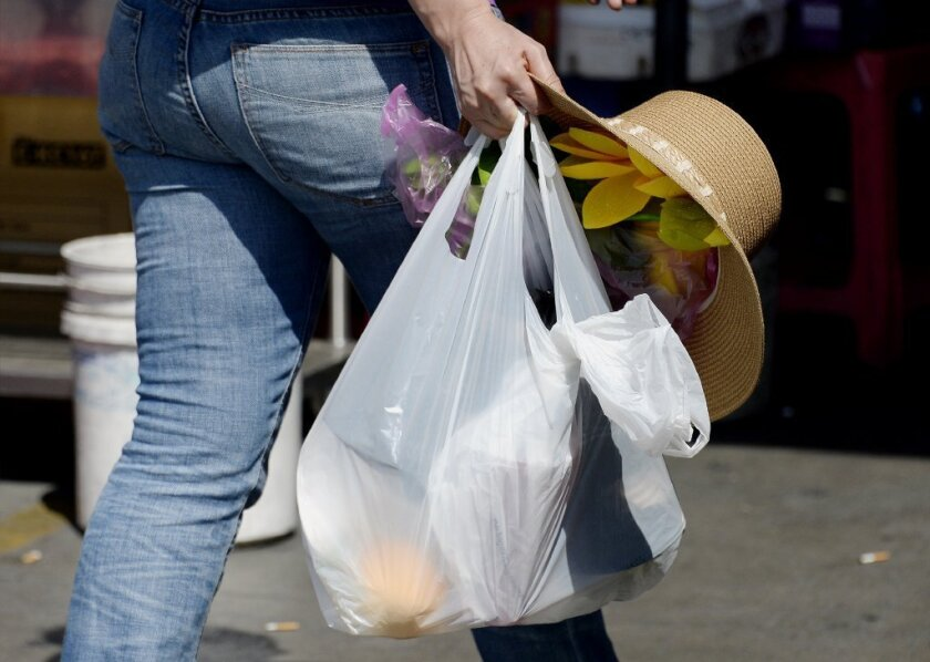 A pedestrian in Los Angeles' Chinatown carries items in a single-use plastic bag.