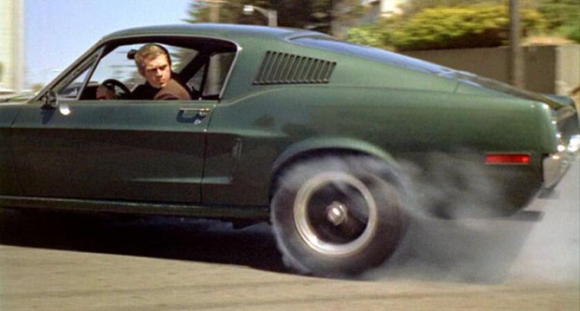 "Steve McQueen behind the wheel of the famous green Mustang in ""Bullitt."""