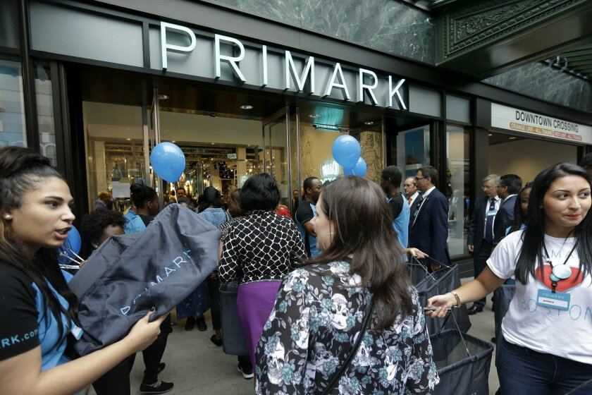 Shoppers, center, are offered bags as they enter a Primark retail store, Thursday, Sept. 10, 2015, in the Downtown Crossing neighborhood of Boston. Irish retailer Primark opened its first U.S. location in Boston Thursday at the former site of the original Filene's Basement. (AP Photo/Steven Senne)