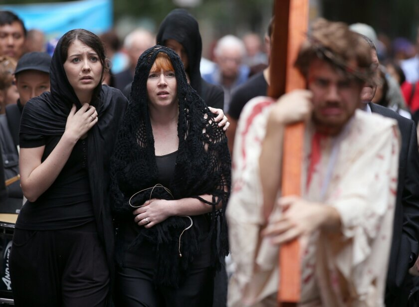 Brendan Paul, right, plays the part of Jesus as supporters follow during a re-enactment of the crucifixion of Christ in Sydney, Friday, April 3, 2015. Members of the Wesley Mission use a modern interpretation of the recreation of Jesus' journey to the cross before a Good Friday service is held. (AP Photo/Rick Rycroft)