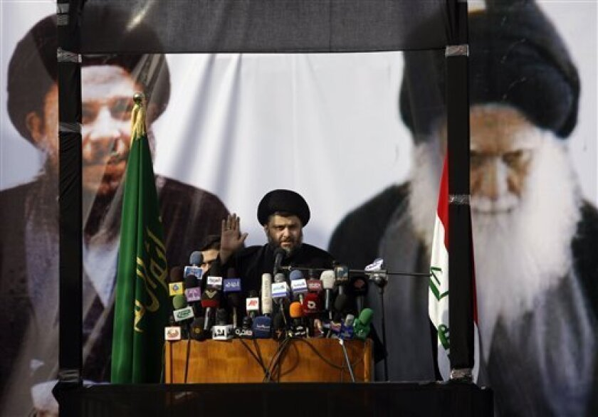 """Shiite cleric Muqtada al-Sadr gestures during his first public appearance since returning from nearly four years of self-imposed exile in Najaf, south of Baghdad, Iraq, Saturday, Jan. 8, 2011. The powerful cleric was greeted by shouts of """"Long live the leader"""" outside his ancestral home in the holy Shiite city of Najaf. Al-Sadr appears beneath a graphic banner bearing the pictures of his brother, the late Ayatollah Mohammed Baqir al-Sadr, left, and father, the late Grand Ayatollah Mohammed Sadiq al-Sadr, right. (AP Photo/Karim Kadim)"""