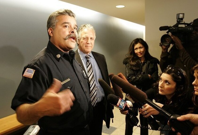 Fire Capt. John Ghiotto (left) talks with reporters outside the court room as his attorney, Charles LiMandri,  listens.