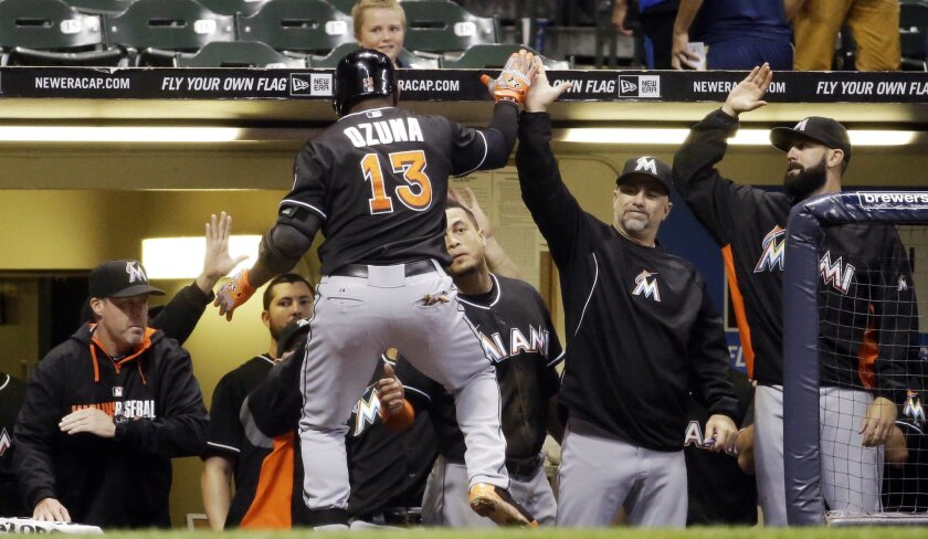 Miami Marlins' Marcell Ozuna is congratulated after hitting a home run during the ninth inning of a baseball game against the Milwaukee Brewers on Tuesday, Sept. 9, 2014, in Milwaukee. (AP Photo/Morry Gash)