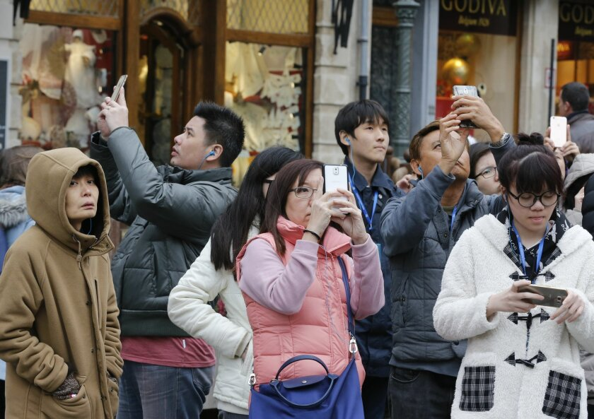Japanese tourists take pictures on the Grand Place in Brussels, Belgium, Friday, Nov. 27, 2015. Brussels lowered its terror alert from four, the highest, to three. (AP Photo/Michael Probst)