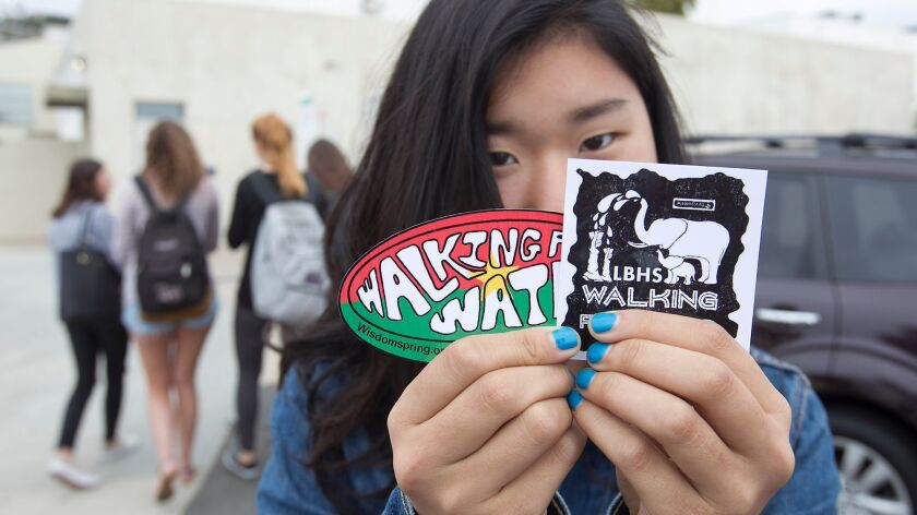 Utah Urushido shows off stickers she created for the Walk for Water event this weekend at the Laguna