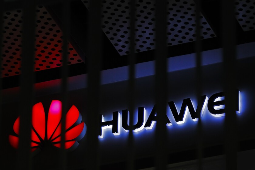 A logo of a Huawei retail shop is seen through a handrail at a Beijing office building.