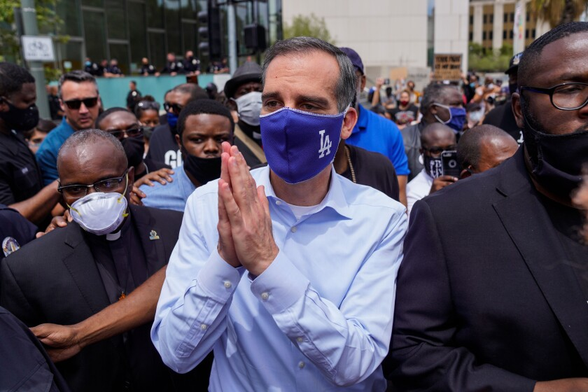L.A. Mayor Eric Garcetti puts his hands together in a gesture of prayer with protesters and clergy in downtown Los Angeles.