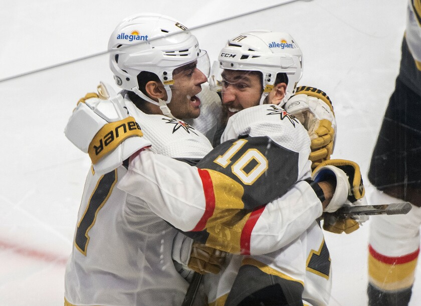Vegas Golden Knights' Nicolas Roy (10) celebrates his game-winning goal against the Montreal Canadiens with teammate Max Pacioretty in overtime of Game 4 in an NHL Stanley Cup playoff hockey semifinal in Montreal, Sunday, June 20, 2021. (Graham Hughes/The Canadian Press via AP)