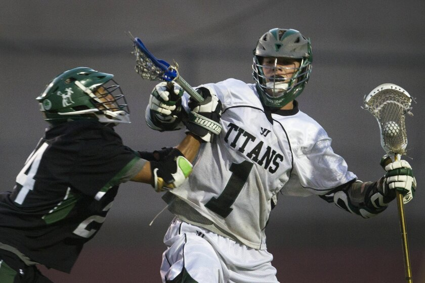 Poway's Jack Woodard (shown earlier in the playoffs) battles an opponent as the Titans went on to win the section Open Division championship with an 8-7 triumph over Torrey Pines on Saturday.