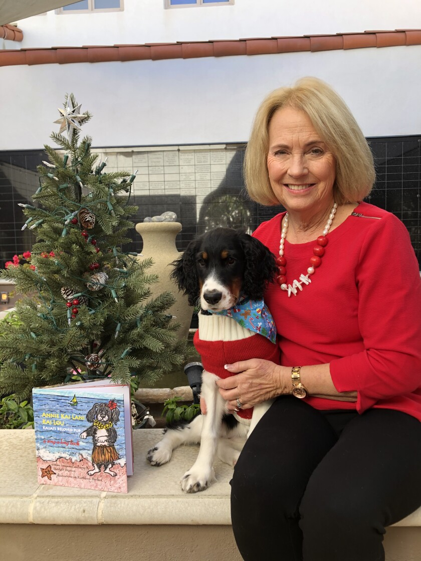 """La Jollan Bridget Burton, also known as Barbara Burton Graf, and puppy Scarlett with Burton's book """"Annie Kai Lani Kai Lou."""""""