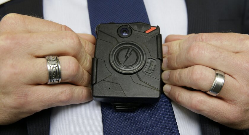 FILE -- In this Feb. 19, 2015 file photo, Steve Tuttle, vice president of communications for Taser International, demonstrates one of the company's body cameras for The Associated Press during a company-sponsored conference hosted by Taser at the California Highway Patrol Headquarters in Sacramento, Calif. Lawmakers have sought $1 million for the CHP to develop a program for its officers to use body cameras. (AP Photo/Rich Pedroncelli, file)