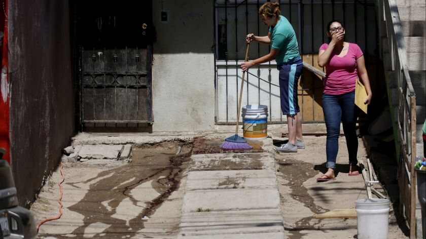A woman washes blood from the driveway where her husband was shot and killed in Tijuana in April 2017.