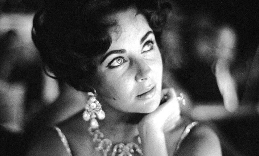 Elizabeth Taylor watches her fiance Eddie Fisher as he performs on stage at the Tropicana in Las Vegas in 1959.