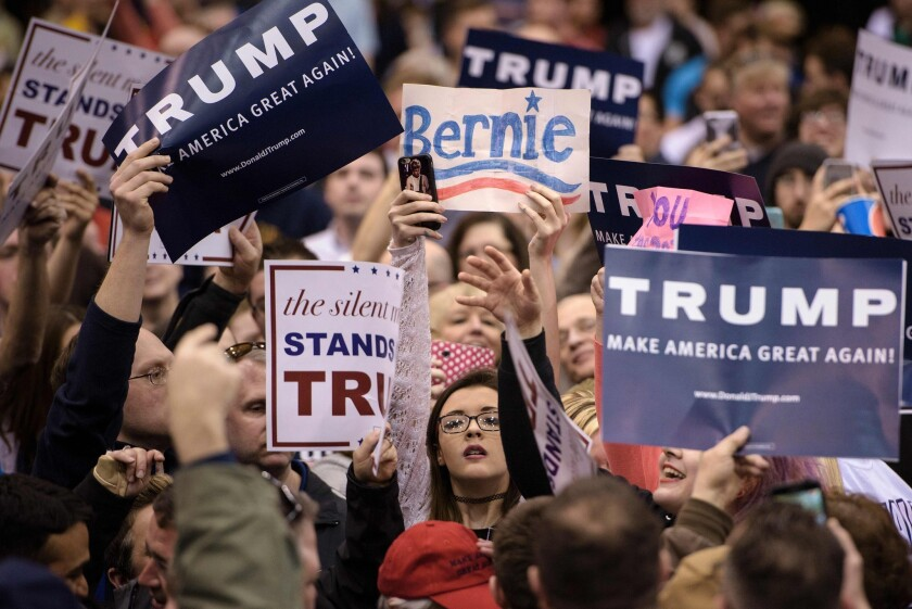 A supporter of Democratic candidate Bernie Sanders holds up a sign during a Donald Trump rally Saturday in Cleveland. The Republican candidate blames Sanders supporters for instigating violence at a Trump event in Chicago, which was canceled for security reasons.