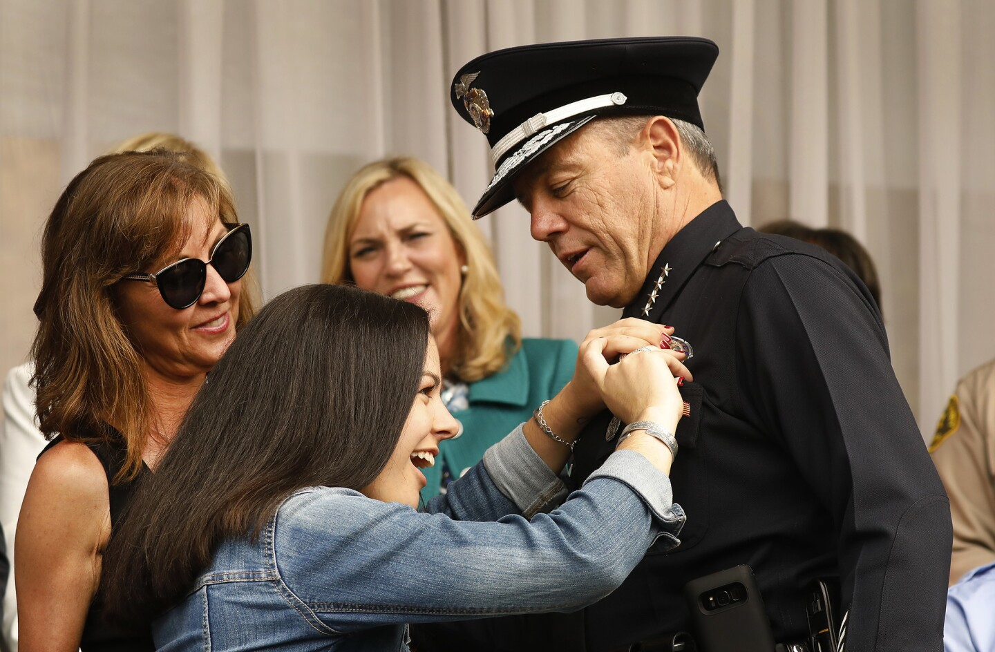 Haley Moore, 18, daughter of the new LAPD Chief Michel Moore, places his new badge as his wife, Cindy Moore, left, watches at the swearing-in ceremony of Los Angeles' 57th police chief.