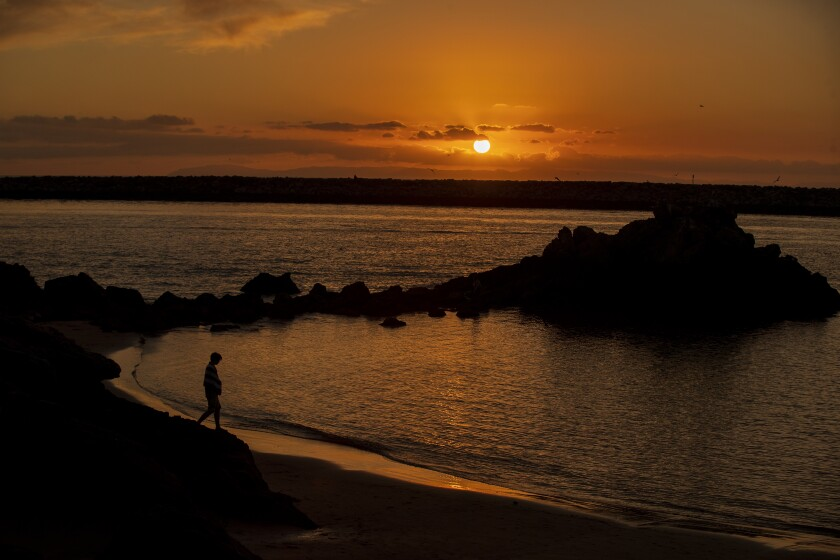A beachgoer is silhouetted by a scenic sunset at Corona del Mar State Beach on Jan. 8, 2020. Warm weather is on tap for Southern California this weekend.