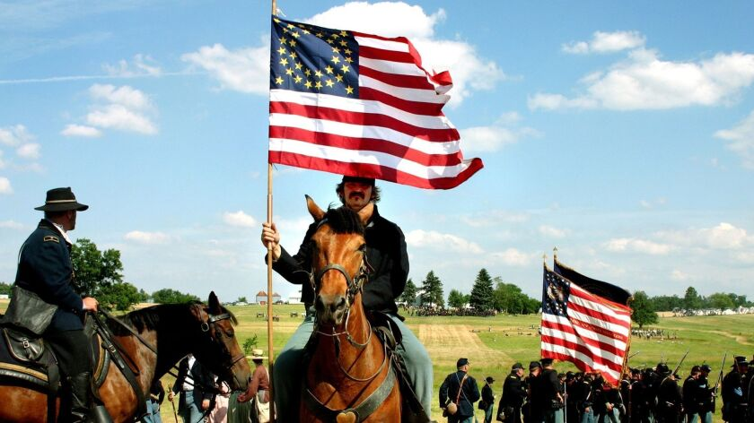 A flag bearer rides behind the Union line during a recent Civil War re-enactment in Gettysburg, Pa.