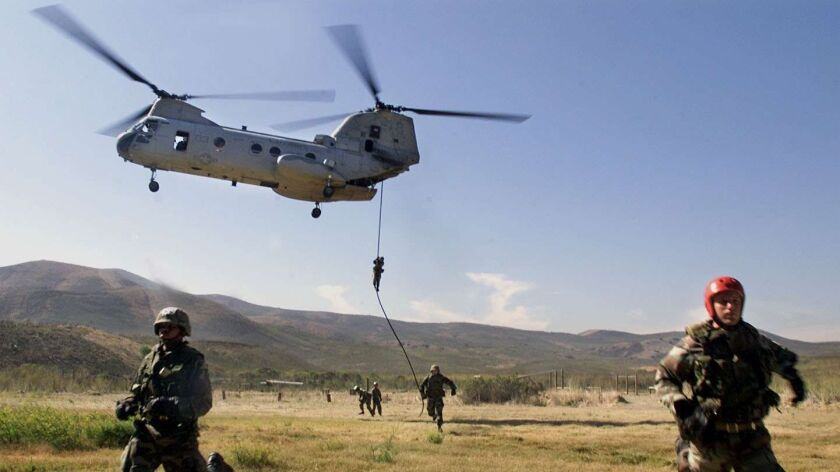U.S. Marines run clear of a CH–46 Seaknight helicopter after fast-rope decending training at Camp Pendleton.