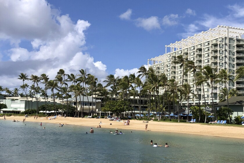 People hang out on the beach and play in the water in front of the Kahala Hotel & Resort in Honolulu.