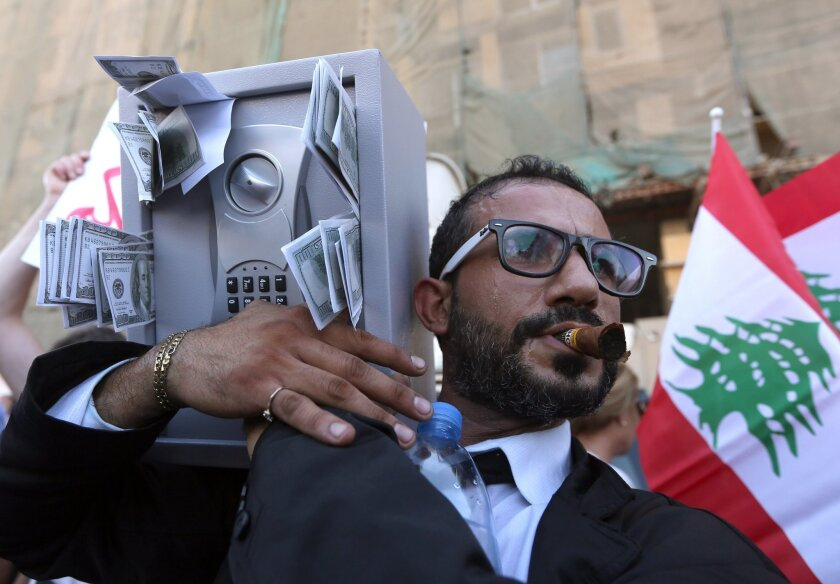 A Lebanese anti-government protester acts the role of a Lebanese politician holding a safe with fake money sticking out, during a demonstration against the trash crisis and government corruption, in downtown Beirut, Lebanon, Saturday, Aug. 29, 2015. hat has dominated Lebanon since the end of the country's civil war in 1990. (AP Photo/Bilal Hussein)