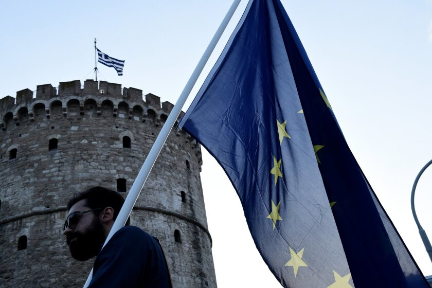 A pro-Euro demonstrator holds a European Union flag during a rally in the northern Greek port city of Thessaloniki, Thursday, July 9, 2015. Hopes that Greece can get a rescue deal that will prevent a catastrophic exit from the euro rose on Thursday, after key creditors said they were open to discus