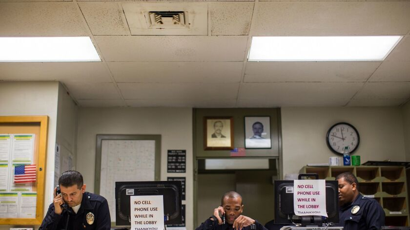 LAPD officers answer phones in the lobby of the Southeast Community Police Station, which has been found to have black mold on the ceiling HVAC vents.