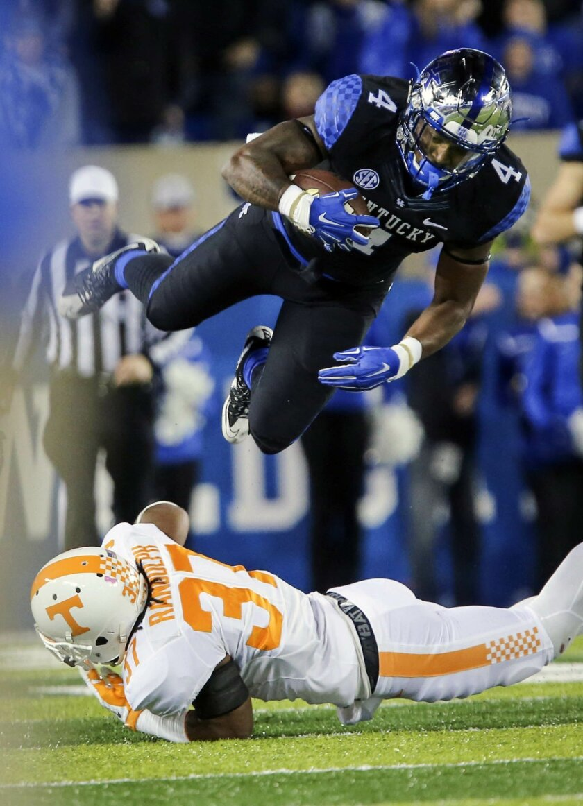 Kentucky running back Mikel Horton dives over Tennessee defensive back Brian Randolph during the first half of an NCAA college football game Saturday, Oct. 31, 2015, in Lexington, Ky. (AP Photo/David Stephenson)