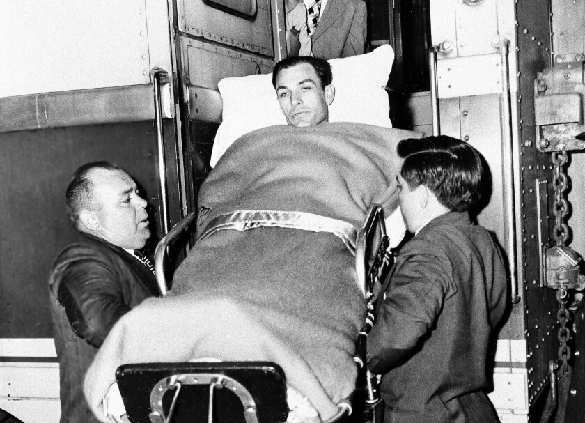 Golfer Ben Hogan is taken off a train in Fort Worth after being hospitalized following a car crash in 1949.