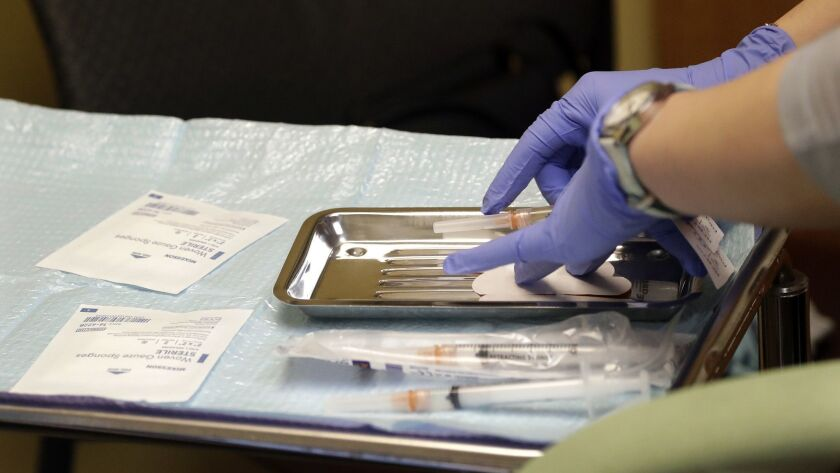 File - In this Feb. 13, 2019, file photo, a health care worker prepares syringes, including a vaccin