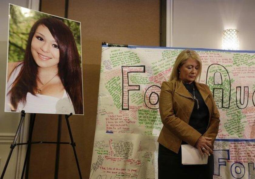 Sheila Pott, mother of Audrie Pott, who committed suicide after a sexual assault, stands by a photograph of her daughter and message board during a news conference in April.