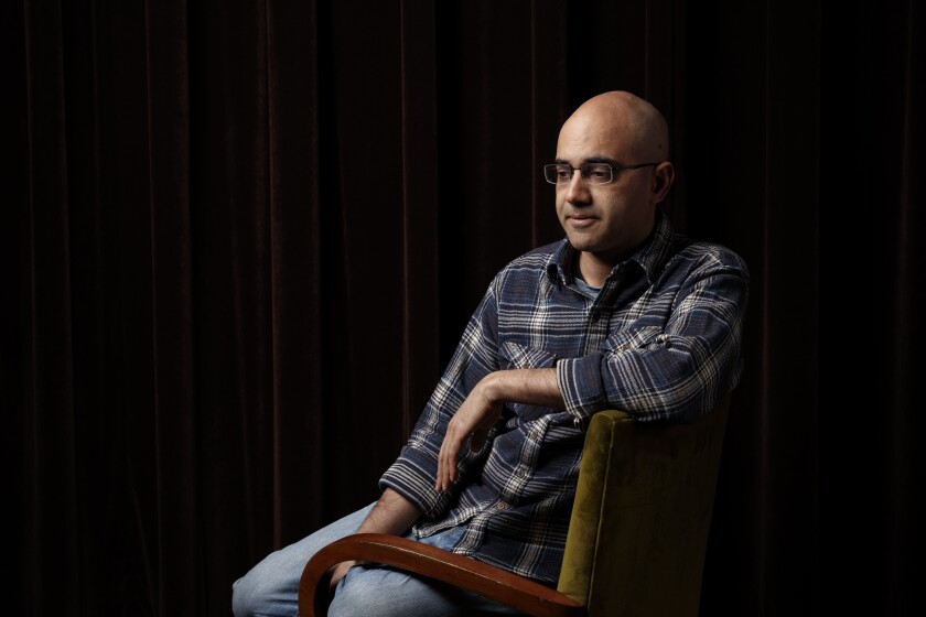 Writer Ayad Akhtar sits in a chair.