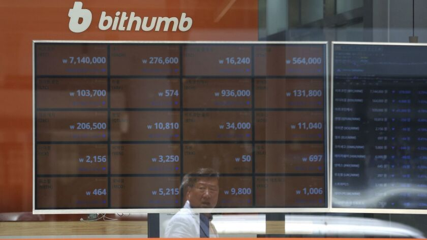 A man is reflected on a screen showing the prices of bitcoin at Bithumb cryptocurrency exchange in S