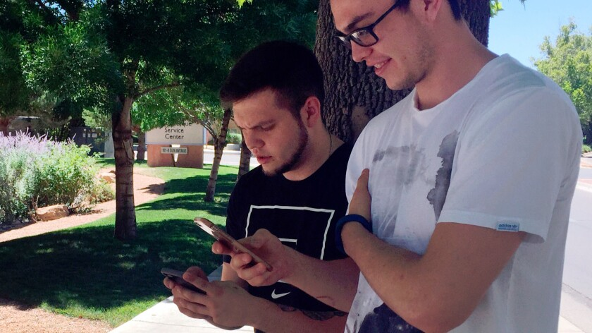 "Damien Hyatt, 23, left, and his brother, Eron Hyatt, 21, right, play ""Pokemon Go,"" while walking around an office building. Law enforcement agencies nationwide has issued warnings over the game."