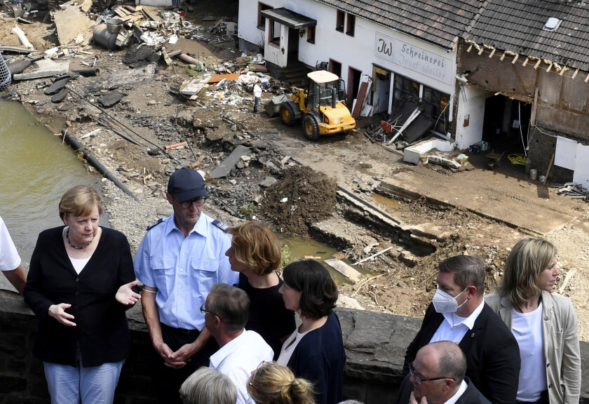 German Chancellor Angela Merkel, left, and the Governor of the German state of Rhineland-Palatinate, Malu Dreyer, rear third left, are seen on a bridge in Schuld, western Germany, Sunday, July 18, 2021 during their visit in the flood-ravaged areas to survey the damage and meet survivors. After days of extreme downpours causing devastating floods in Germany and other parts of western Europe the death toll has risen. (Christof Stache/Pool Photo via AP)