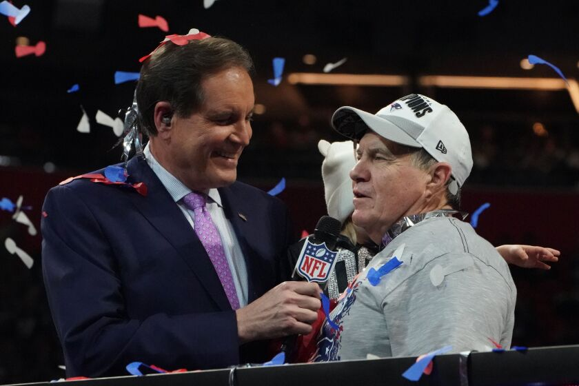 Sportscaster Jim Nantz interviews Patriots coach Bill Belichick after the Patriots beat the Rams in the Super Bowl.