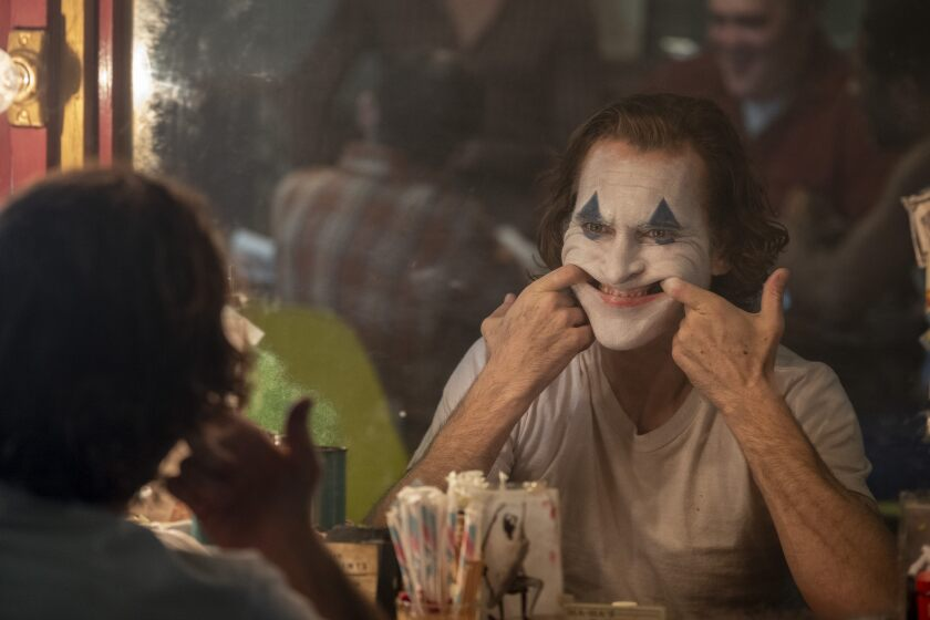 "Joaquin Phoenix in ""Joker."" He is seated and reflected in a mirror, with his index fingers hooked in the sides of his mouth."