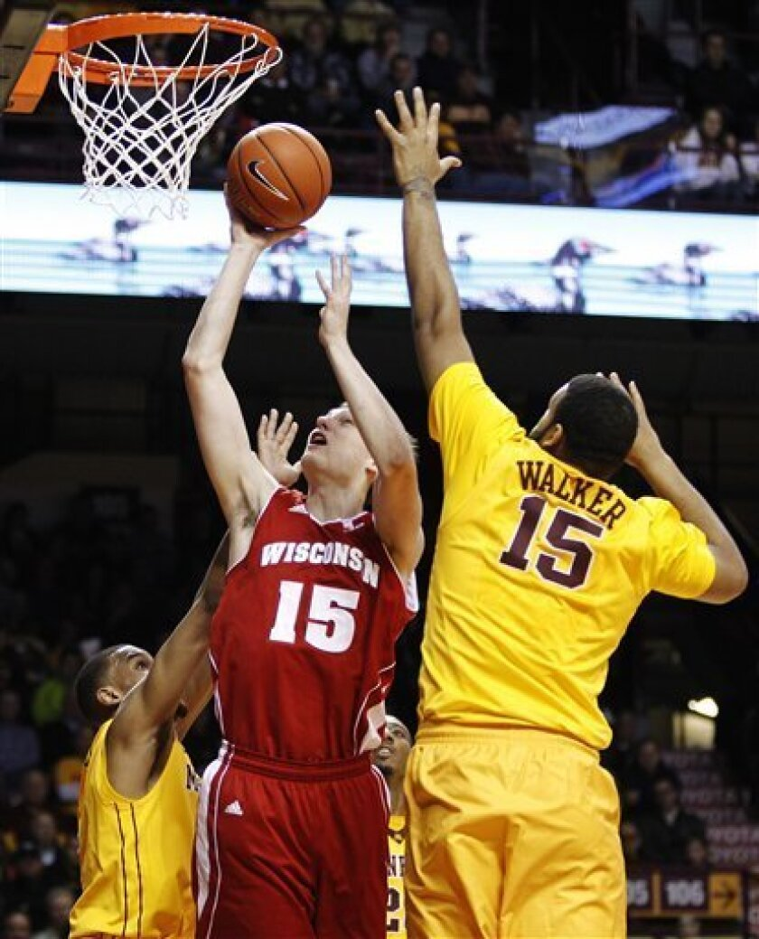Wisconsin's Sam Dekker (15) is fouled by Minnesota's Andre Hollins, left, as he makes the basket and Minnesota's Maurice Walker (15) defends during the first half of an NCAA college basketball game, Thursday, Feb. 14, 2013, in Minneapolis. (AP Photo/Genevieve Ross)