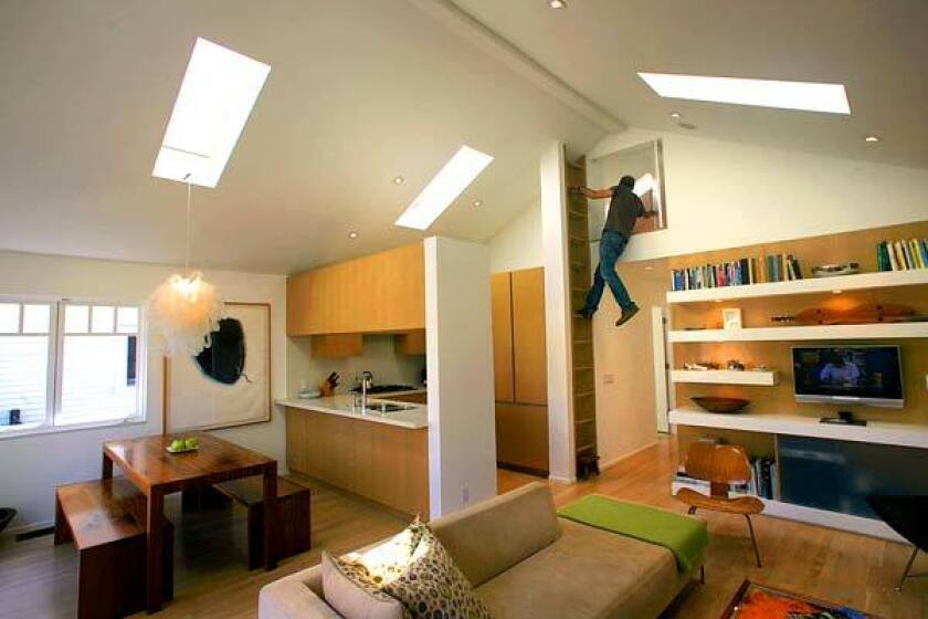 "A ladder serves as an architectural element and climbs to a carpeted tree house-like loft, boosting family space by 120 square feet. ""It is a great way to get an extra room for kids' sleepovers,"" Ritch says. The L-shaped hallway leads to three bedrooms and the children's bathroom. A door at the short end of the ""L"" leads to the backyard and Ritch's detached studio."