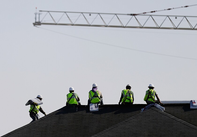 Construction workers rest while unloading supplies on a rooftop in Atlanta on March 23.
