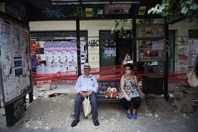 People wait for a bus in the northern Greek port city of Thessaloniki on June 30. Greek Finance Minister Yanis Varoufakis confirmed that the country would not be able to make a payment that is due the International Monetary Fund on Tuesday night.