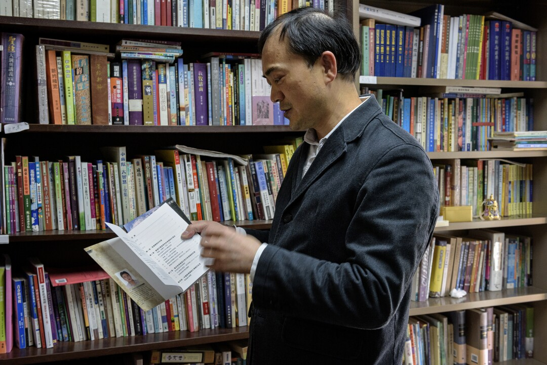 A man flips through a book in front of a bookshelf filled with books