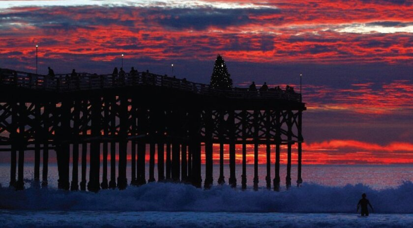 The sun sets behind a packed Crystal Pier in Pacific Beach on Monday.