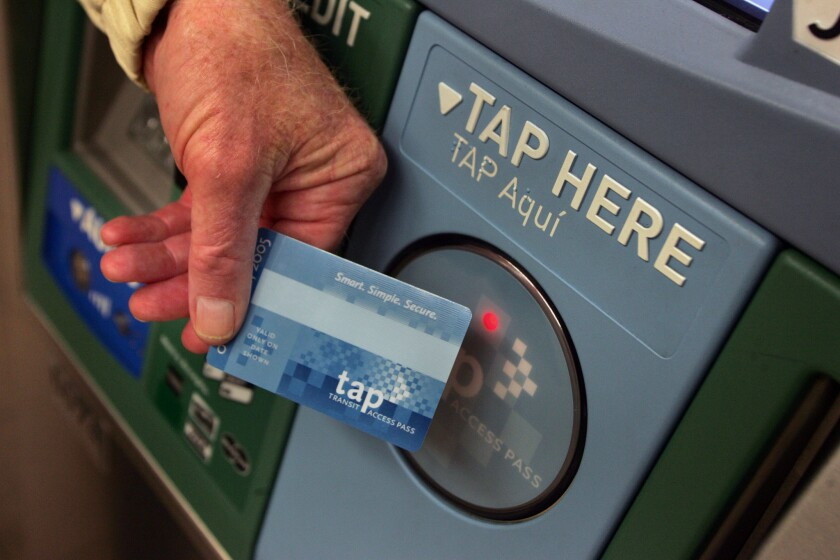 A Metro rider touches his TAP card against a ticket vending machine in downtown Los Angeles.
