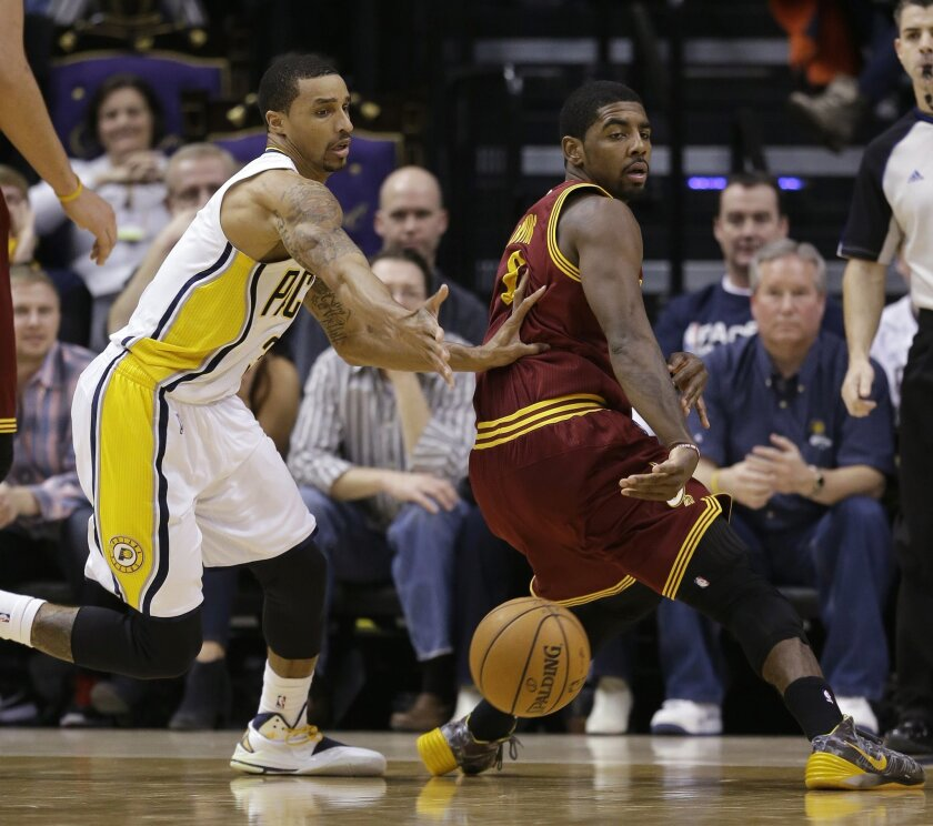 Cleveland Cavaliers' Kyrie Irving, right,  makes a pass while being defended by Indiana Pacers' George Hill (3) during the second half of an NBA basketball game Tuesday, Dec. 31, 2013, in Indianapolis. Indiana defeated Cleveland 91-76. (AP Photo/Darron Cummings)
