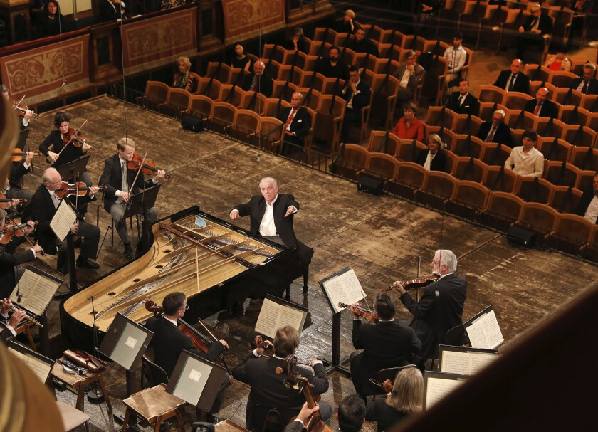 This June 5, 2020 photo released by the Wiener Philharmoniker Orchestra shows pianist Daniel Barenboim conducting the Vienna Philharmonic Orchestra in Vienna, Austria. Its 2,854-seat Musikverein, considered by many the world's most beautiful concert hall, was filled with only 100 people Friday for the first of three days of programs with Barenboim. (Dieter Nagl/Wiener Philharmoniker Orchestra via AP)