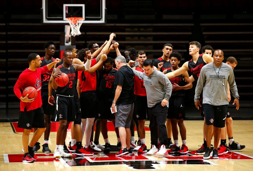 SDSU coach Brian Dutcher and his players gather for their first official practice last season.