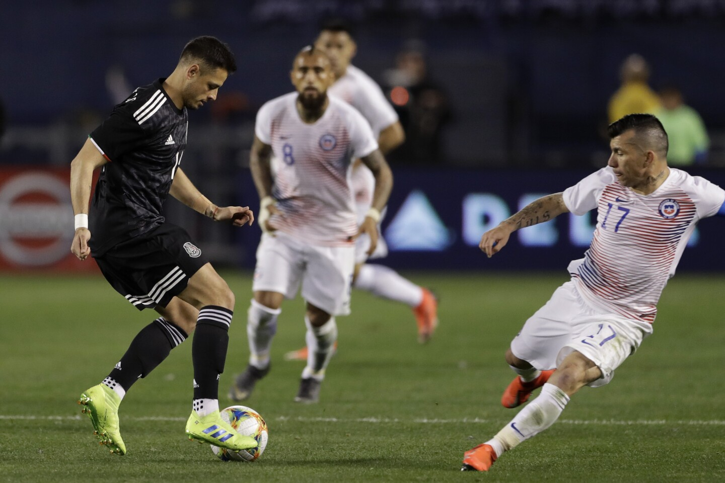 Mexico's Javier Hernandez, left, dribbles the ball as Chile's Gary Mendel, right, defends during the second half of an international friendly soccer match Friday, March 22, 2019, in San Diego. (AP Photo/Gregory Bull)